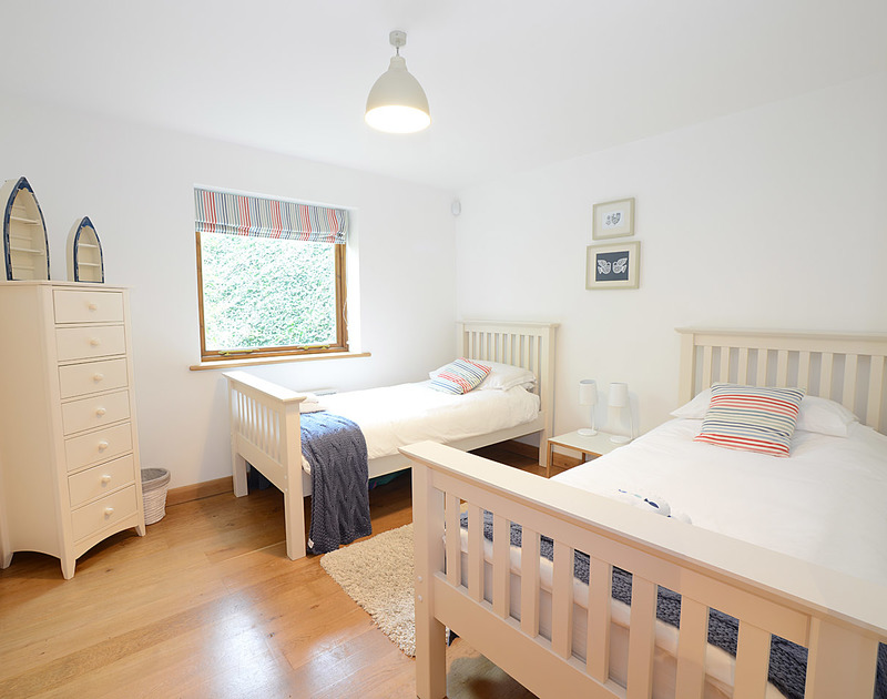 8 Sandy Hills twin bedroom with smart wooden flooring and plenty of natural light.