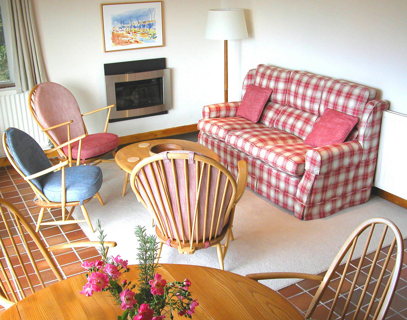 The attractive, colourful sitting room of Rosevallen, a holiday house at Daymer Bay, Cornwall, with its electric fire.