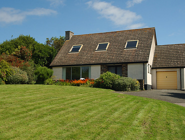The large lawned garden and front exterior of Rosevallen, a charming holiday cottage to rent at Daymer Bay, Cornwall