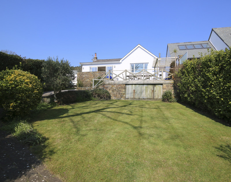 The south-facing lawned garden and rear view of Little Strand, a holiday rental in Rock, Cornwall