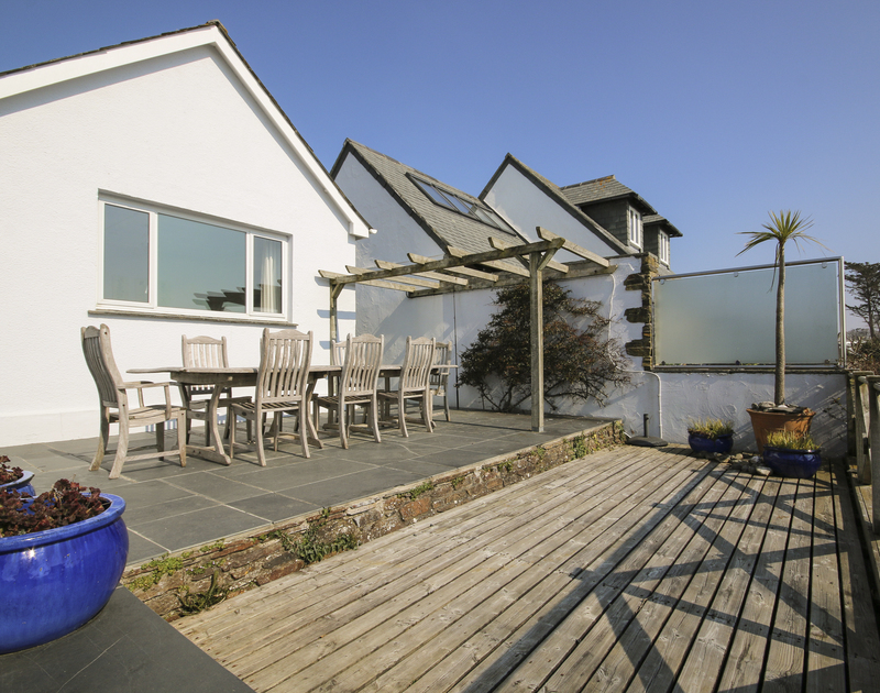 The large terrace on two levels at Little Strand, a perfect holiday house at Rock, Cornwal, with wooden decking and slate paving.