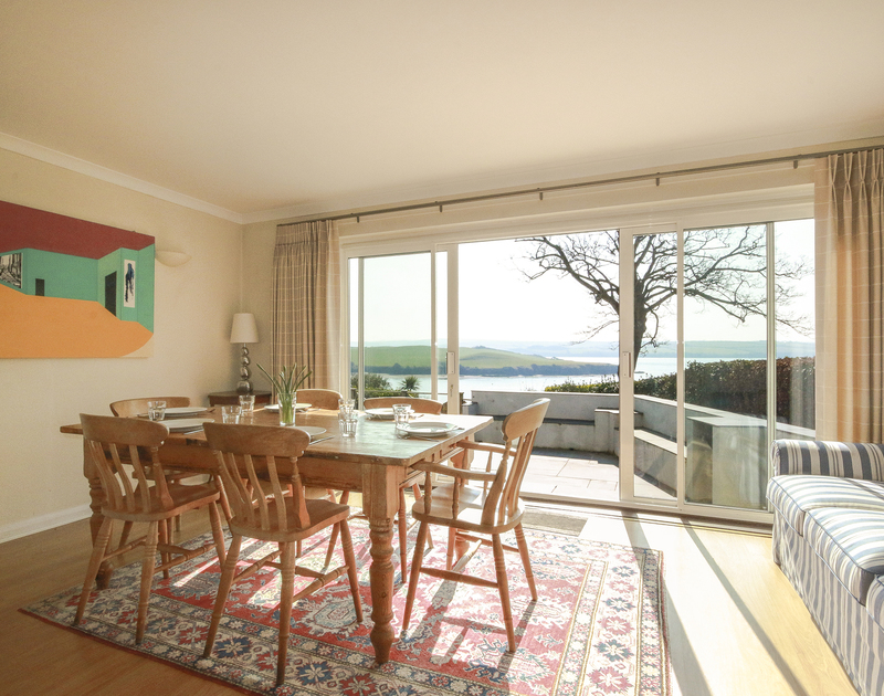 The light-filled dining area of Little Strand, a holiday house in Rock, Cornwall, with glass doors to the terrace.