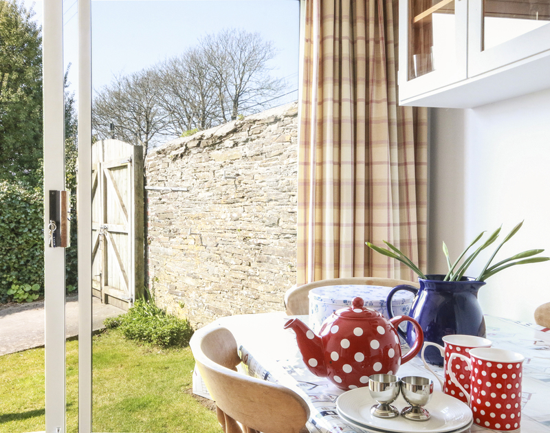 The breakfast table by the french windows leading to the garden of Little Strand, a holiday house at Rock, Cornwall