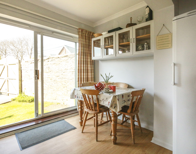 The attractive breakfast room of Little Strand, an idyllic holiday rental in Rock, Cornwall, with sliding doors to the garden.
