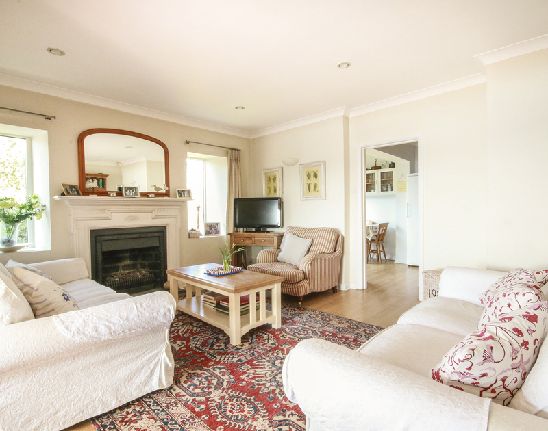 The comfy, well-furnished sitting room of Little Strand, a holiday rental in Rock, Cornwall, with TV and gas fireplace.