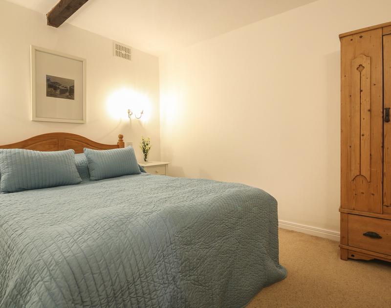 Double bedroom in self catering holiday rental Church Hill Flat with pine furniture and no window in Port Isaac, Cornwall.