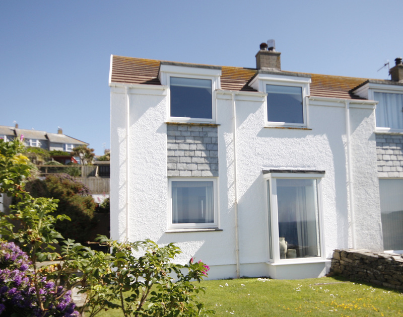 The exterior of 3 Overcliff, a self-catering holiday house in Port Isaac, Cornwall, with lawned garden.