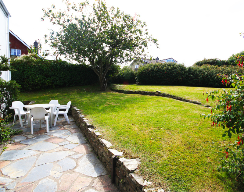 The sunny patio and terraced elevated lawn of White House, a holiday rental near Rock, Cornwall