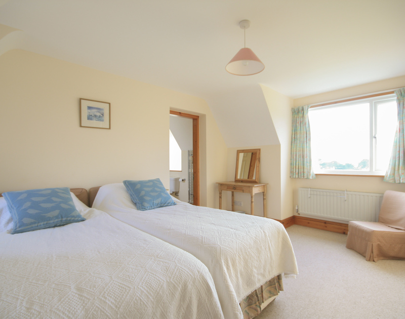 An attractive, light twin bedroom with lovely views at Seaworthy, a lovely holiday rental near Daymer Bay, North Cornwall.