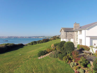 The exterior and large garden of Harbour Lights, a self-catering holiday house in Rock, Cornwall, with its panoramic views of the Camel Estuary.