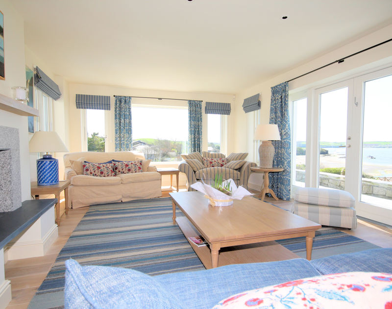 Light pours into the sitting room while the picture windows offer magnificent sea views at Harbour Lights, a self-catering holiday house in Rock, Cornwall.