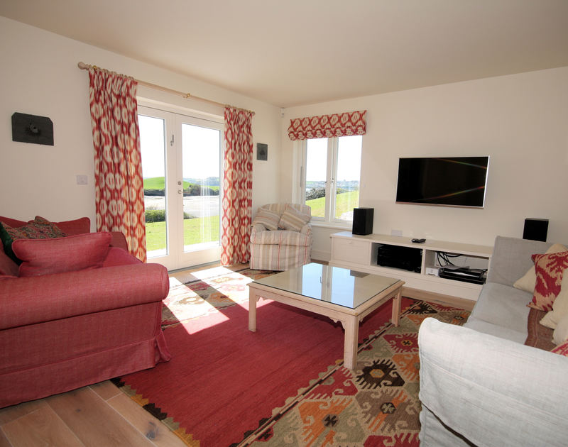 The tastefully decorated TV room/ second sitting room at Harbour Lights, a luxury holiday house to rent in Rock, Cornwall, offers wonderful water views