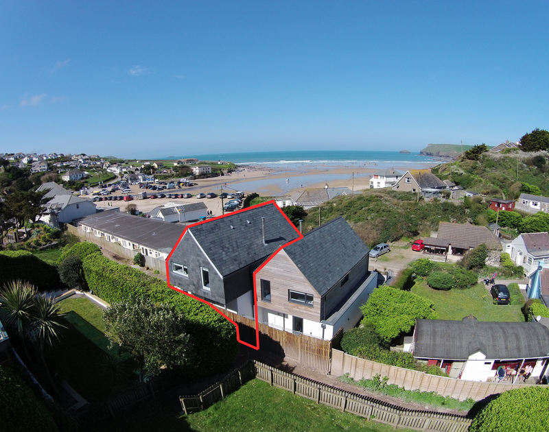An aerial view of the rear of The Beach House, self-catering holiday house in Polzeath, with the beach and sea in the background.