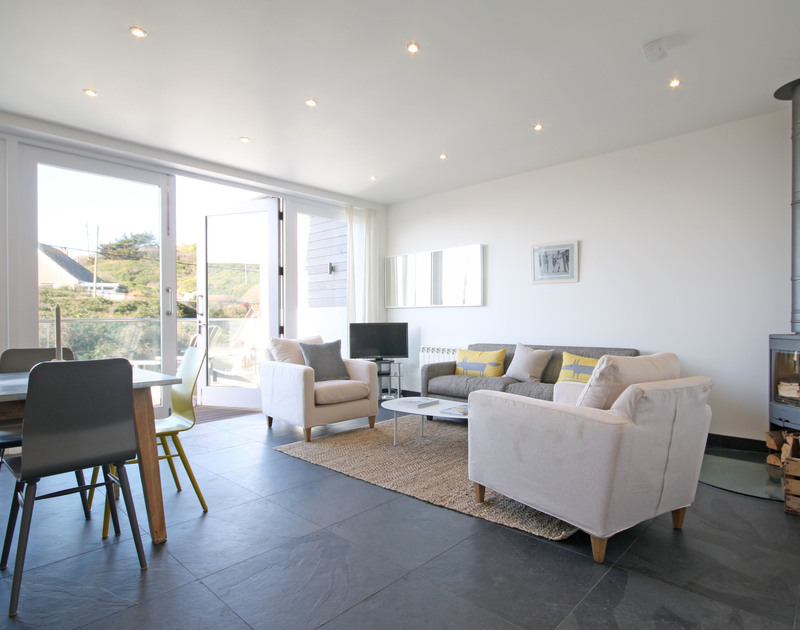Spacious and light living area of The Beach House, self-catering holiday house in Polzeath, Cornwall, with doors to deck.