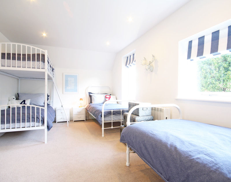 Stylishly decorated bunk room at The Beach House, holiday rental in Polzeath, with 2 single beds and 1 set of bunk beds.