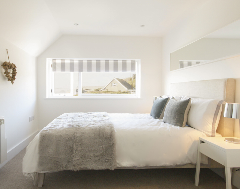 A stylish bedroom with seaviews at The Beach House, luxury holiday rental in Polzeath, Cornwall