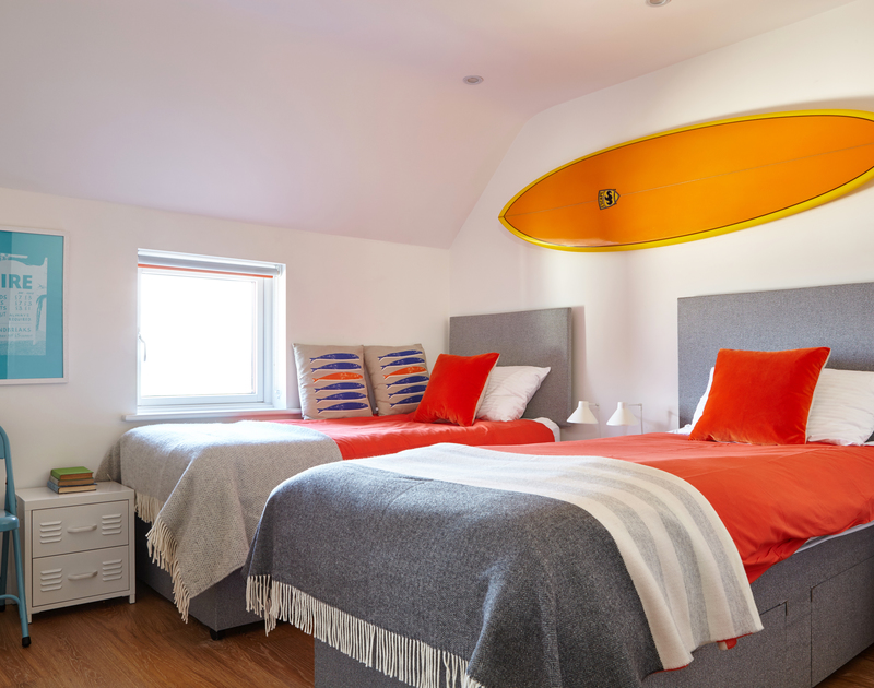 Colourful furnishings and surfboard wall art at Epphaven, gorgeous holiday house at Polzeath, Cornwall.