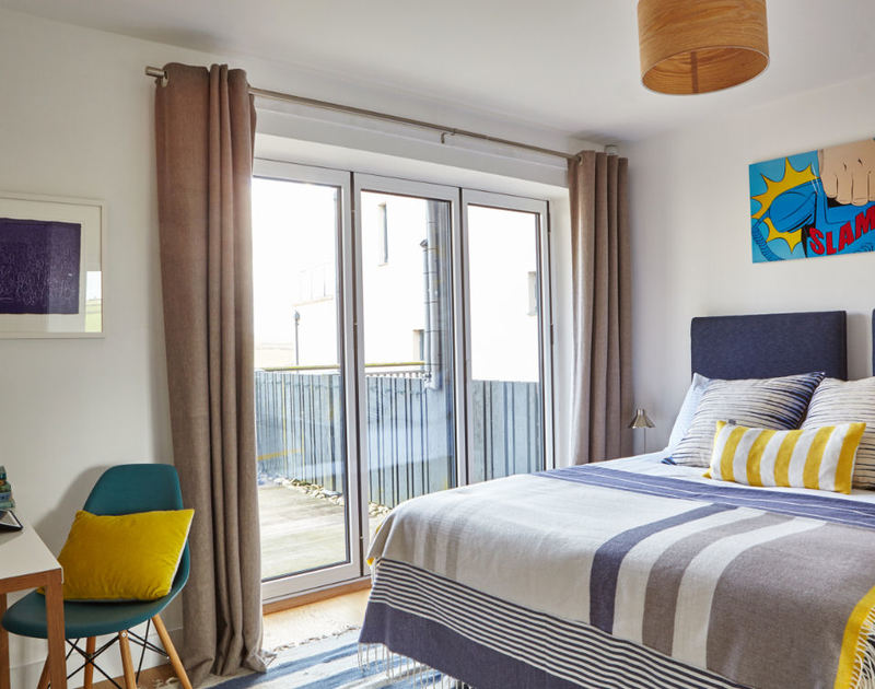 Beautifully decorated bedroom at Epphaven, a holiday house to rent at Polzeath, with folding doors leading to the deck.