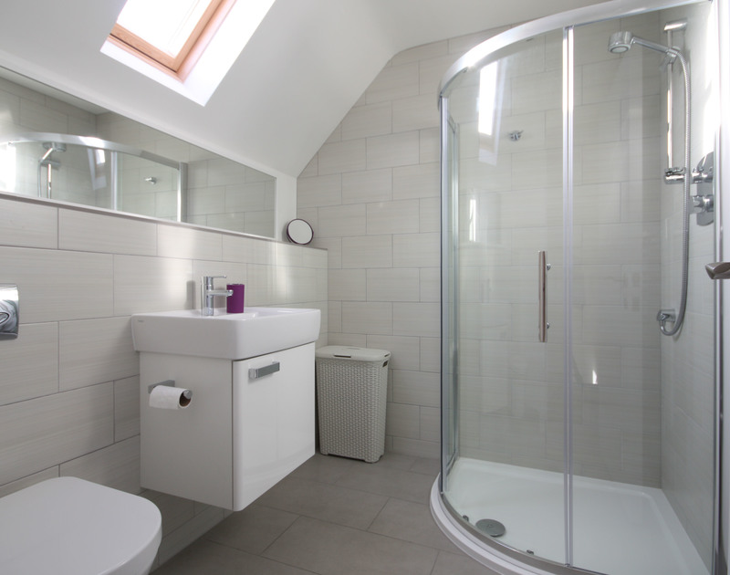 A smart and light bathroom with velux window at Epphaven, a stunning holiday house in Polzeath, Cornwall