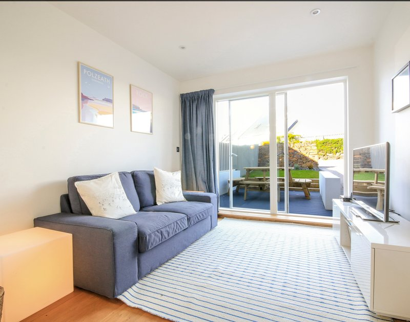 The elegant snug/TV room with french windows out to the garden in 3, The Sands a luxurious self catering holiday retreat in Polzeath, North Cornwall.