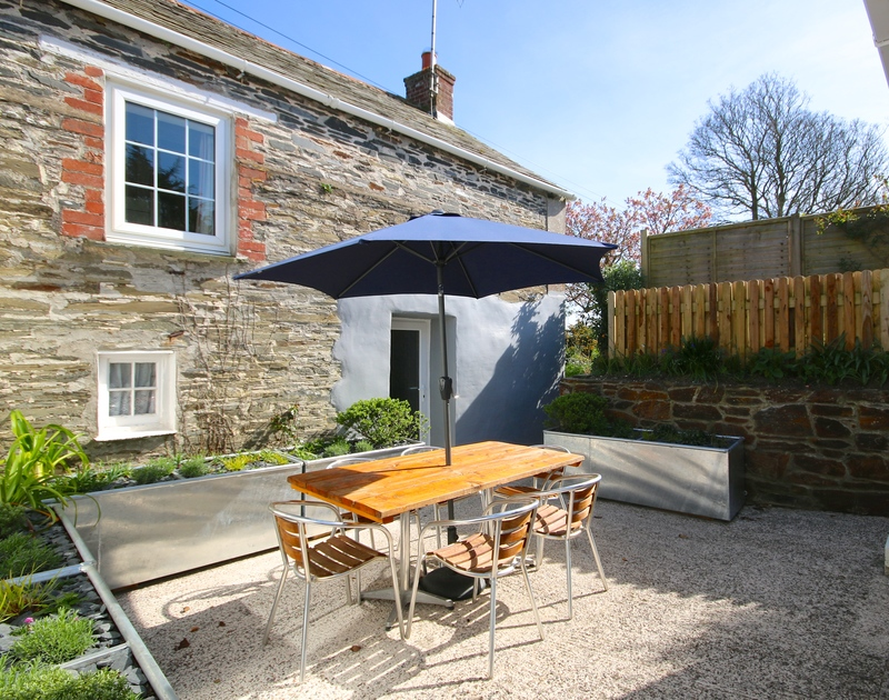The sunny ,enclosed courtyard bordered by pretty planters in St Michaels, a pet friendly holiday retreat in Porthilly near Rock in Cornwall.