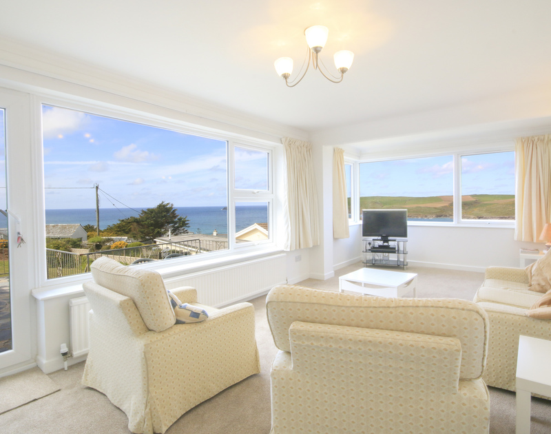 The bright lounge and huge windows showing the sea views of Newland and Pentire glaze from Tremelyn in Polzeath, Cornwall.