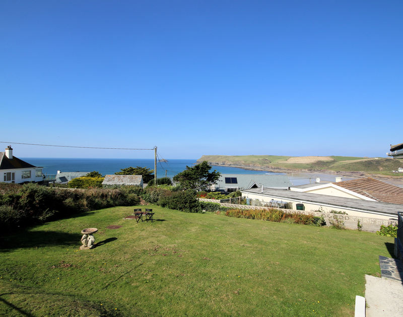 The lawned garden, sea and stunning headland views from self catered bungalow Tremelyn in Polzeath,Cornwall.