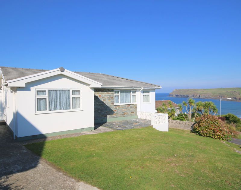 The exterior of holiday rental Tremelyn showing the views towards Pentire Head and lawned garden at Polzeath,Cornwall.