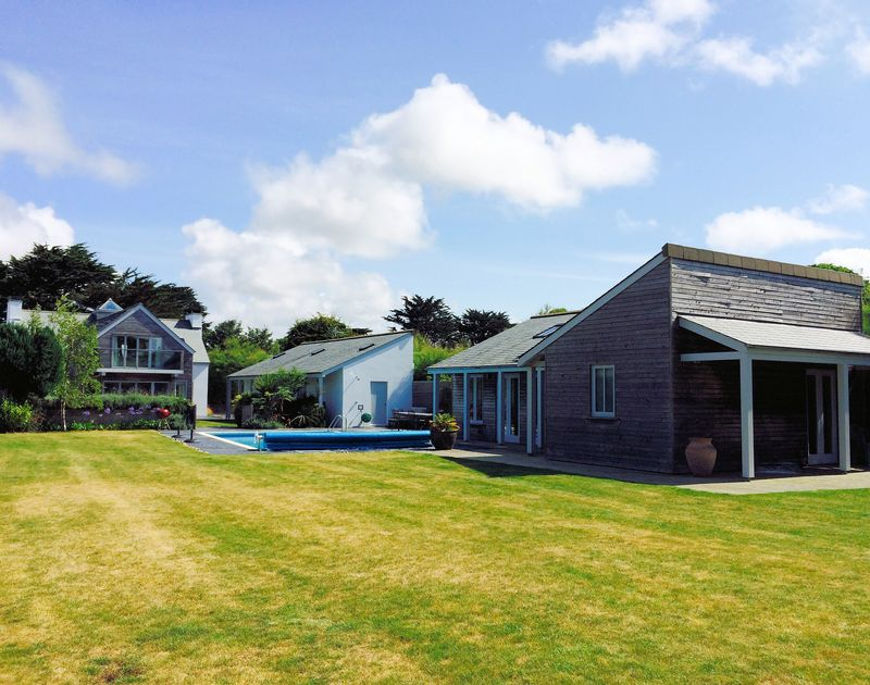 The large and sunny lawned gardens, swimming pool and exterior view of Trerokken's pool house sleeping four guests in Rock, Cornwall.