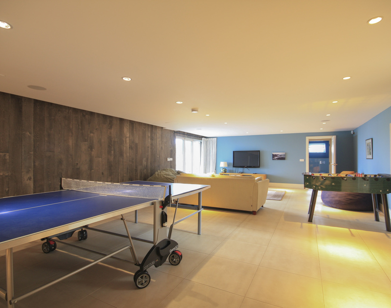 The games room at Greenaway Reach,  a self catering holiday home to rent near Daymer, North Cornwall with a table tennis and football table has a TV and patio doors to the garden,