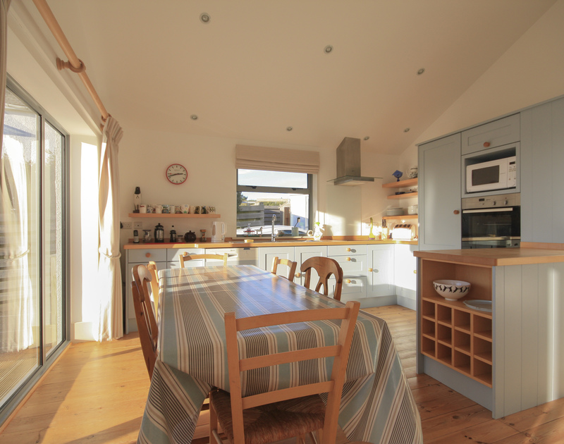 The attractive and modern kitchen and dining table with loads of light from the huge windows in Yaffles, a holiday house to rent in Daymer Bay, Cornwall.