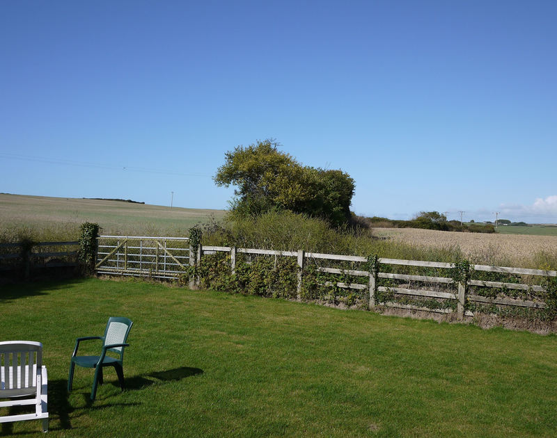 The well kept back garden and lovely rural outlook from Yaffles, a self catering holiday rental in Daymer bay on the North Cornish coast.