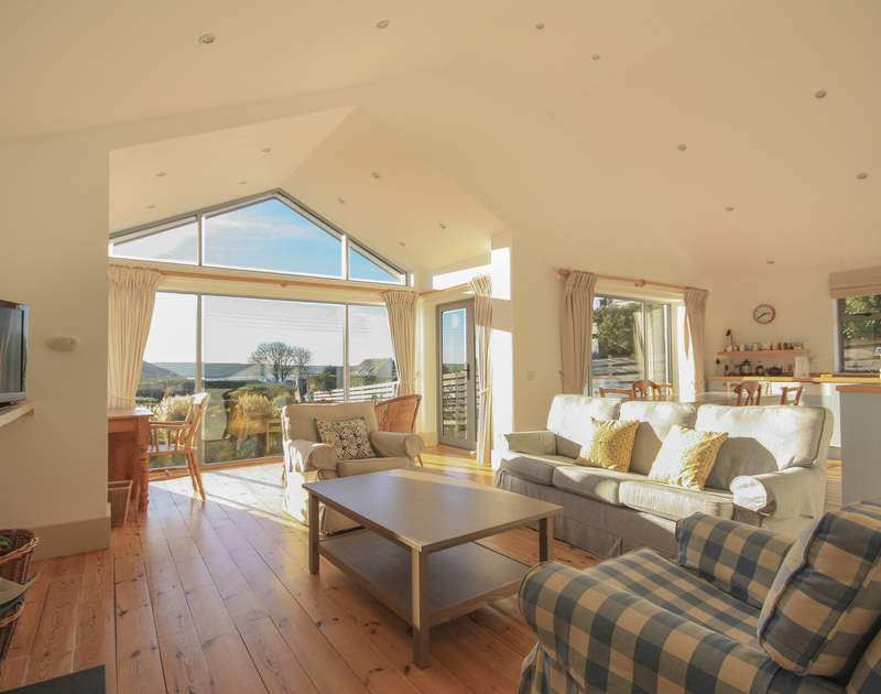 The light-filled sitting room, wooden floorboards, large windows and views from Yaffles, a self catering holiday house to rent in Daymer Bay on the North Cornish coast.