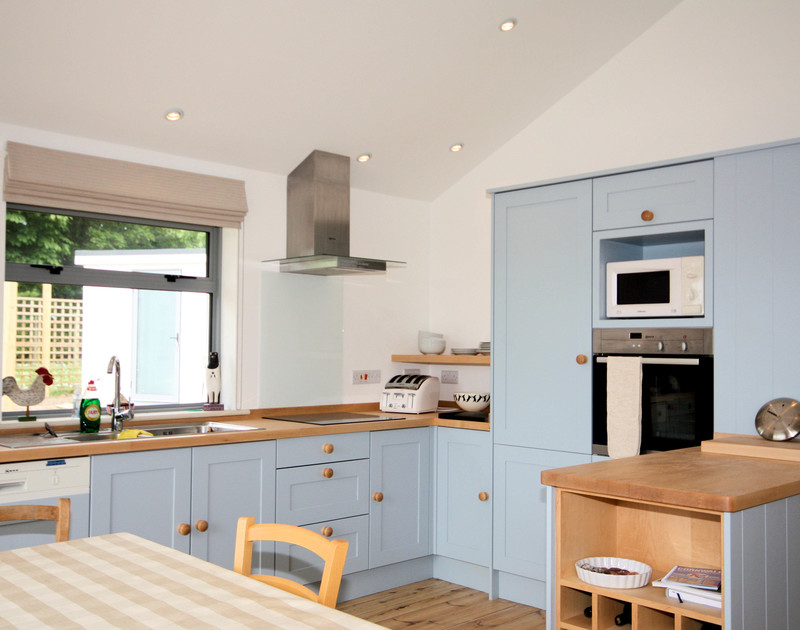 The pretty, blue modern kitchen with numerous cooking facilities in Yaffles, a well-equipped self catering holiday rental in Daymer Bay on the North Cornish Coast.
