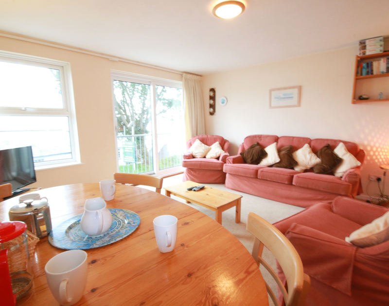 The cosy sitting and dining room of Slipway 6, a holiday cottage to rent in Rock, Cornwall