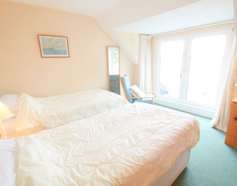 Twin bedroom and balcony with estuary views at Slipway 6, holiday cottage in Rock, Cornwall