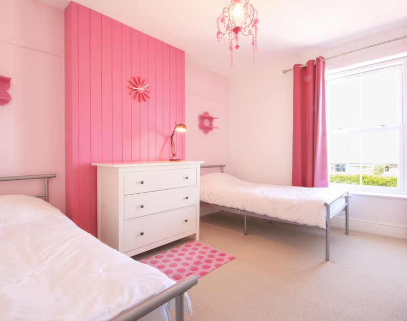 Pops of bright pink decorate this twin room at Crewsnest, a luxury holiday house in Rock, Cornwall