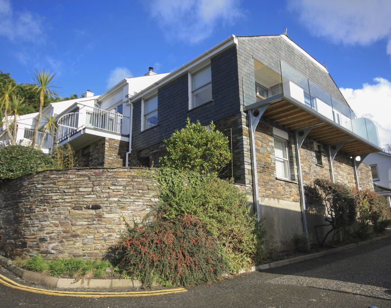 The exterior view of the end of terrace Slipway 23, a holiday cottage in Rock, Cornwall, with its first floor balcony.