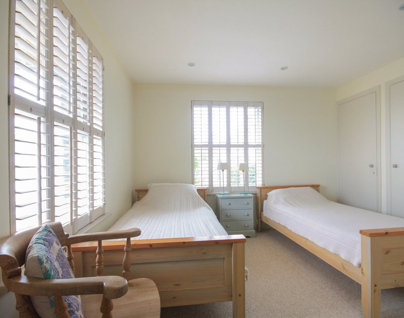 Neat twin bedroom with wooden shuttered windows at Slipway 23, a holiday rental at Rock, Cornwall