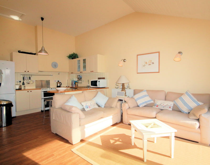 The open plan kitchen and comfortable sitting room in Slipway 12, a welcoming holiday cottage to rent in Rock, Cornwall.