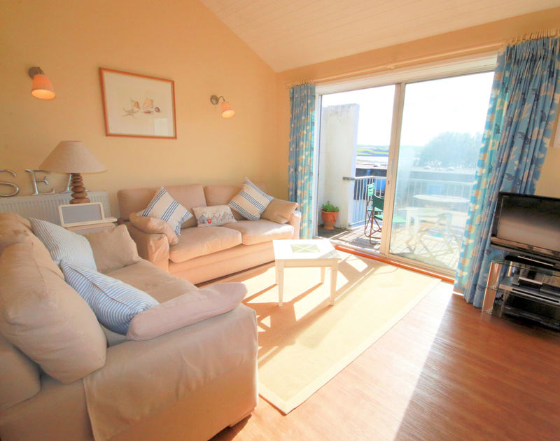 The comfortable, light-filled sitting room with doors to the balcony at Slipway 12, a self catering holiday cottage to rent in Rock, North Cornwall.