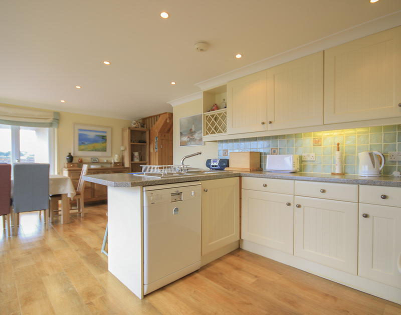 The practical, open-plan kitchen/diner of Little Belz, a holiday house in Polzeath, Cornwall