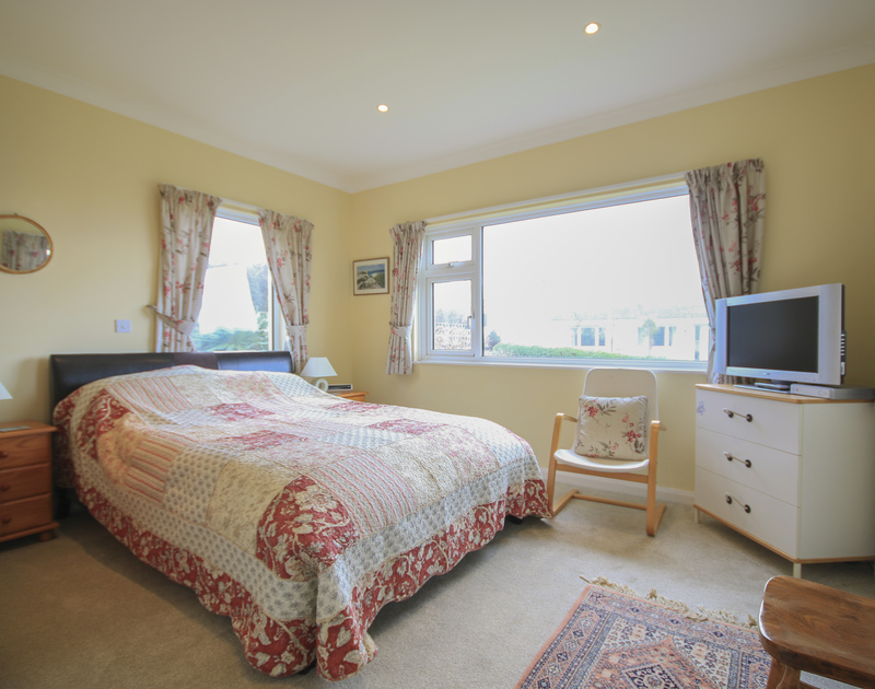 The master bedroom with king size bed of Little Belz, a holiday rental in Polzeath, with flat screen TV.