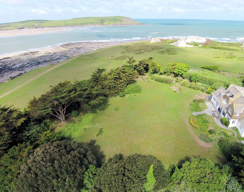 An aerial view of Doom Bar House, a cliff top holiday house at Daymer Bay, Cornwall, with its large lawned garden.