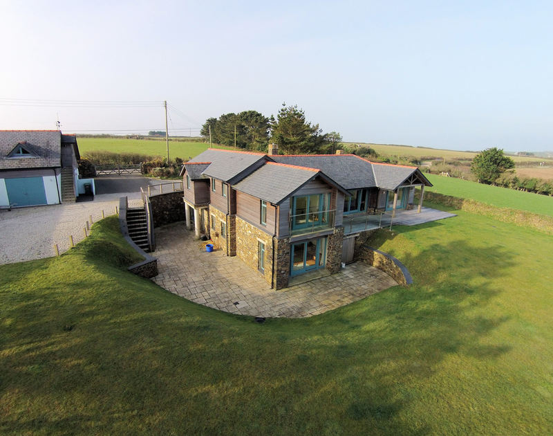 An aerial view showing the beauty, expanse and peaceful situation of Ossco, a luxurious, self catering holiday house to rent in Lundy Bay near Polzeath, North Cornwall.