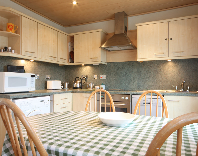 The kitchen and dining table in Pinewood Flat Three, a well located, self catering holiday rental in Polzeath, North Cornwall.