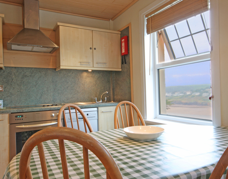The great view of the beach and cliffs towards New Polzeath from the kitchen at Pinewood Flat 3, a self catering holiday rental in Polzeath, Cornwall.