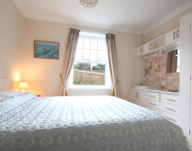 The comfortable double bedroom in Pinewood Flat 3, a self catering holiday rental in Polzeath on the North Cornish Coast.