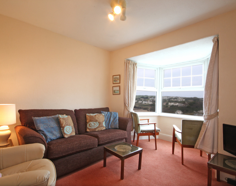 The sitting room with large windows and views over the beach from Pinewood Flat 3, a self catering holiday rental in Polzeath, North Cornwall.
