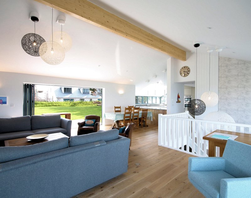 The open plan living area of The Crest, a spacious holiday house in Polzeath, Cornwall, with bifold doors to the garden.